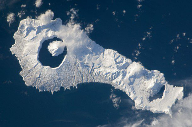 Snow cover highlights the calderas and volcanic cones that form the northern and southern ends of Onekotan Island, part of the Russian Federation in the western Pacific Ocean.