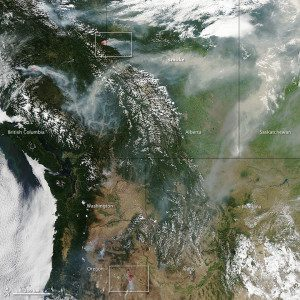 In this July 16, 2014, image captured by the Aqua satellite, forests appear dark green. The snow-capped peaks of the Canadian Rockies are visible in the center of the image. Large banks of white clouds hover over the Pacific Ocean, northern Alberta and Wyoming. Winds pushed long plumes of smoke east toward Alberta and into Saskatchewan.