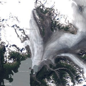 Landsat satellites captured a pair of images showing changes in the glacier and lake during the last 26 years. Landsat 5 acquired this image on Aug. 22, 1987. Snow and ice appear white, and forests are green. The brown streaks on the glaciers are lateral and medial moraines.