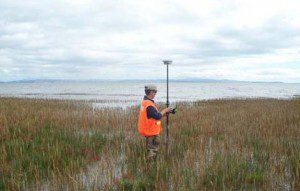 A USGS scientists operates a mobile Global Positioning System receiver to map a saltmarsh, one of many coastal ecosystems under pressure from climate change.