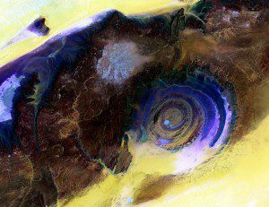 The Eye of the Sahara image is a mosaic of four different Landsat 8 scenes that show the geologic feature in false color. By blending visible and infrared wavelengths (bands), scientists can enhance the visibility of the various rock layers in contrast to the surrounding sand (yellow to white).