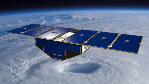 An artist's concept shows one of eight CYGNSS satellites deployed in space above a hurricane.