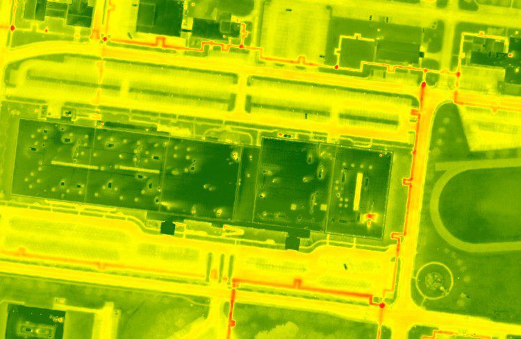 "A FLIR Systems SC8303 sensor captured this color-ramped thermal image, which details subsurface utility concerns identified by red (""hot"") locations detected below the surface. Various plumes also are visible from rooftop penetrations and building facades."