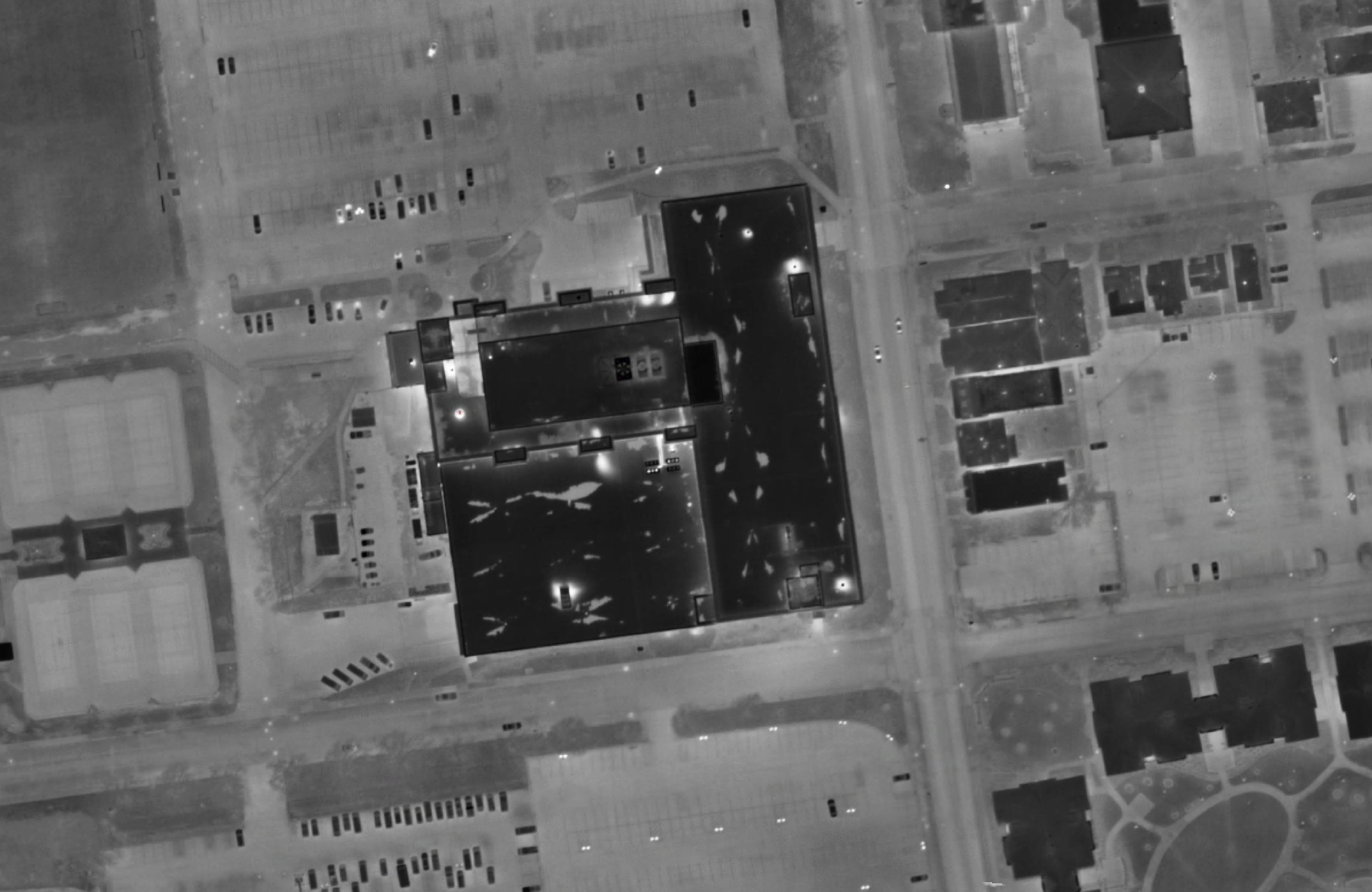 Another image taken by the FLIR sensor shows various temperature anomalies and condition issues on a building roof. Bright spots indicate areas of heat loss and/or moisture retention.