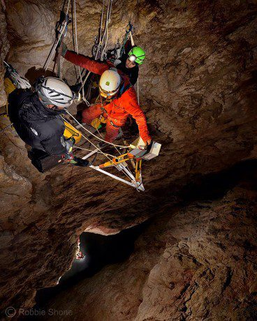 Perched on an aluminium platform several hundred feet above the floor of the great chamber in El Cenote (cave) in the Italian Dolomites, the laser-scanning team carry out a final scan of the upper section of the giant shaft. (Credit: Robbie Shone)