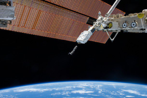 "The Small Satellite Orbital Deployer on the International Space Station was photographed by an Expedition 38 crew member as it deployed a set of Planet Labs' ""Dove"" CubeSats."