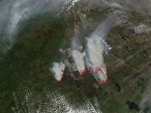 On May 24, the Moderate Resolution Imaging Spectroradiometer (MODIS) on NASA's Aqua satellite captured a natural-color image of fires that continued to burn. Red outlines indicate hot spots where MODIS detected warm surface temperatures associated with fires. (Credit: NASA image by Jeff Schmaltz, LANCE/EOSDIS Rapid Response)